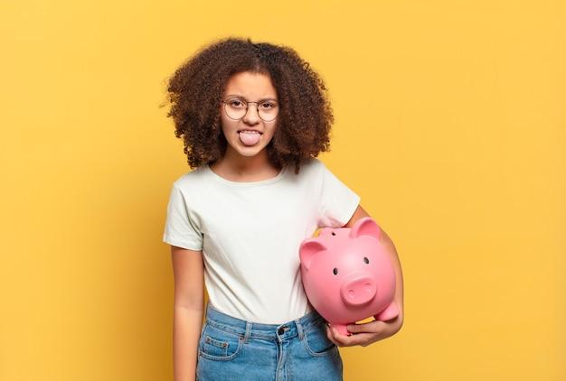 Jolie adolescente afro à la recherche de choc et de surprise avec la bouche grande ouverte, pointant vers soi. concept d'épargne