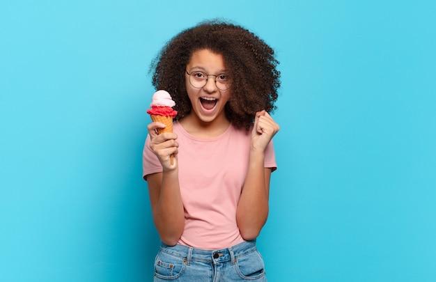 Jolie adolescente afro se sentant choquée, excitée et heureuse, riant et célébrant le succès, disant wow!. concept de crème glacée sumer