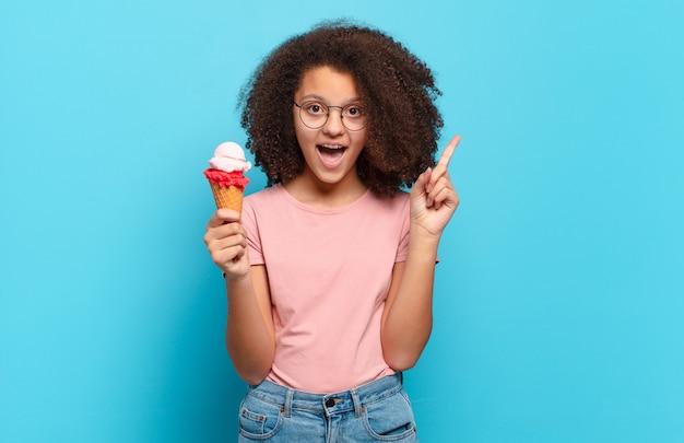 Jolie adolescente afro se sentant comme un génie heureux et excité après avoir réalisé une idée