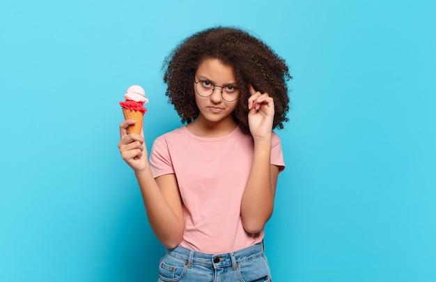 Jolie adolescente afro se sentant confuse et perplexe, montrant que vous êtes folle, folle ou folle
