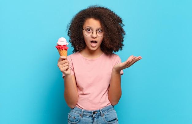 Jolie adolescente afro se sentant extrêmement choquée et surprise, anxieuse et paniquée, avec un regard stressé et horrifié. concept de crème glacée sumer