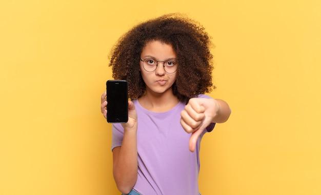 Jolie adolescente afro se sentant fâchée, en colère, agacée, déçue ou mécontente, montrant les pouces vers le bas avec un regard sérieux et tenant une cellule