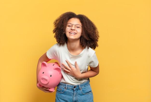 Jolie adolescente afro se sentant heureuse, détendue et satisfaite, montrant son approbation avec un geste correct, souriant. concept d'épargne