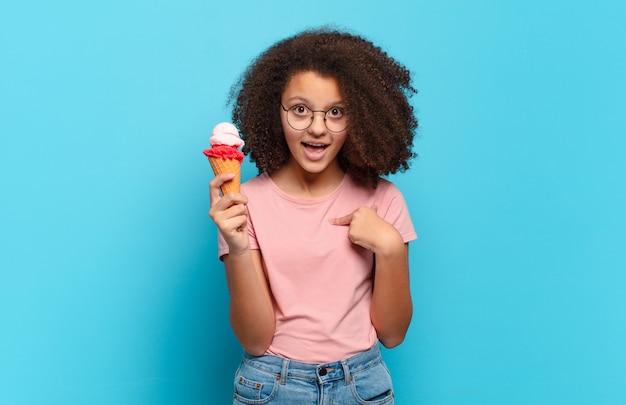 Jolie adolescente afro se sentant heureuse, surprise et fière, se montrant elle-même avec un regard excité et étonné. concept de crème glacée sumer