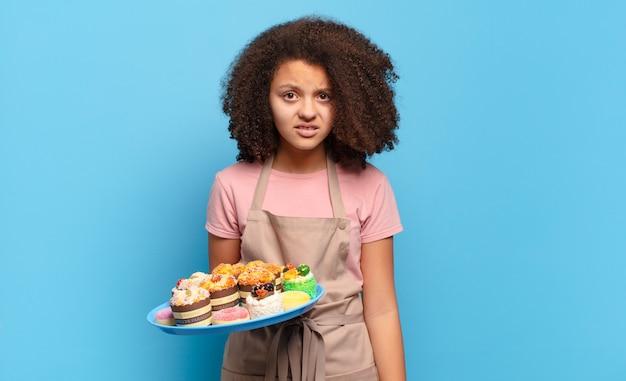 Jolie adolescente afro se sentant perplexe et confuse, avec une expression stupide et abasourdie en regardant quelque chose d'inattendu. concept de boulanger humoristique