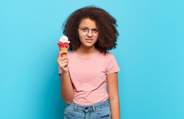 Jolie adolescente afro se sentant perplexe et confuse, avec une expression stupide et abasourdie en regardant quelque chose d'inattendu. concept de crème glacée d'été