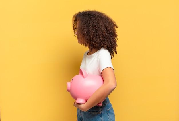 Jolie adolescente afro souriante avec une expression heureuse et confiante avec la main sur le menton, se demandant et regardant sur le côté. concept d'épargne