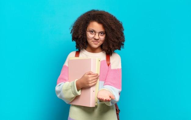 Jolie adolescente afro souriante joyeusement avec un regard amical, confiant et positif, offrant et montrant un objet ou un concept. concept d'étudiant