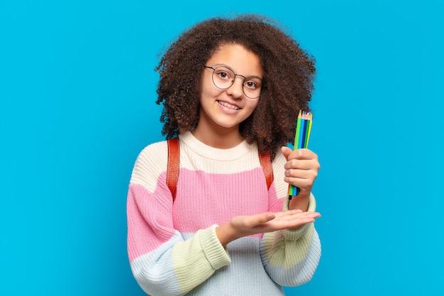 Jolie adolescente afro souriante joyeusement, se sentant heureuse et montrant un concept dans l'espace de copie avec la paume de la main