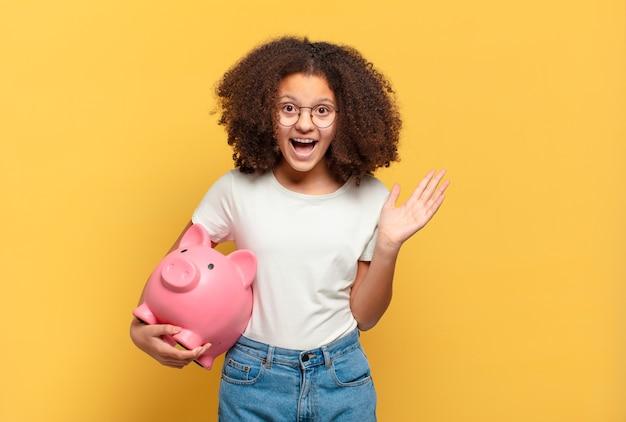 Jolie adolescente afro souriante et semblant amicale, montrant le numéro cinq ou cinquième avec la main vers l'avant
