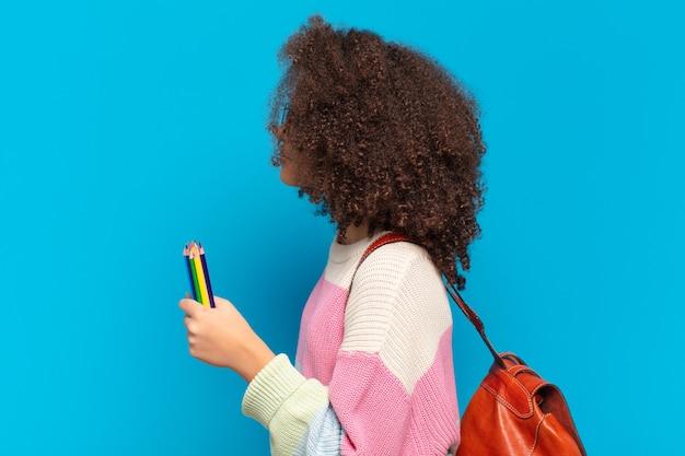 Jolie adolescente afro en vue de profil cherchant à copier l'espace devant, à penser, à imaginer ou à rêvasser. concept d'étudiant