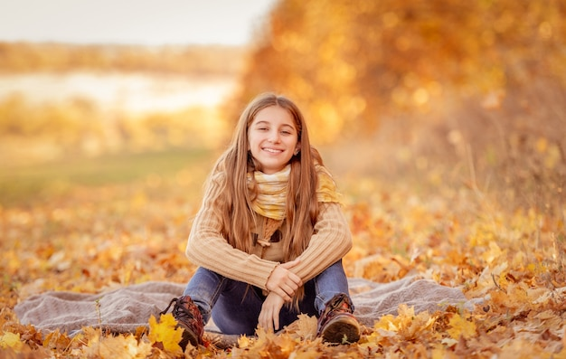 Jolie adolescente assise dans des feuilles jaunes avec une tasse de thé