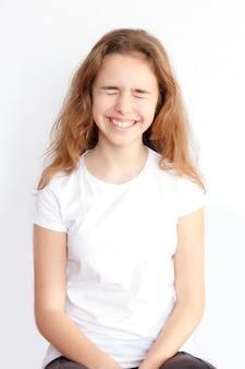 Une jolie adolescente aux cheveux longs fait très drôle de visage et rit aux yeux fermés