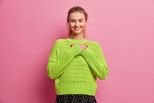 Jolie adolescente aux cheveux peignés sourit exprime agréablement son appréciation fait un geste de gratitude