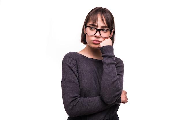 Jolie adolescente brune avec une impatience et une expression ennuyée isolée sur blanc
