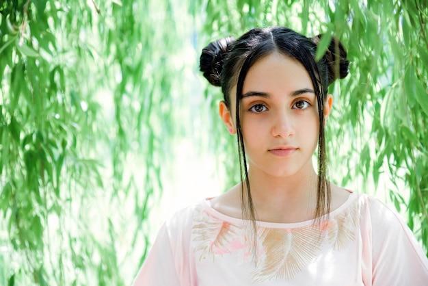 Jolie adolescente avec des chignons regardant la caméra tout en se tenant au milieu du feuillage vert du saule pleureur en été