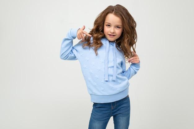 Jolie adolescente dans un sweat à capuche bleu posant sur un fond clair avec copie espace