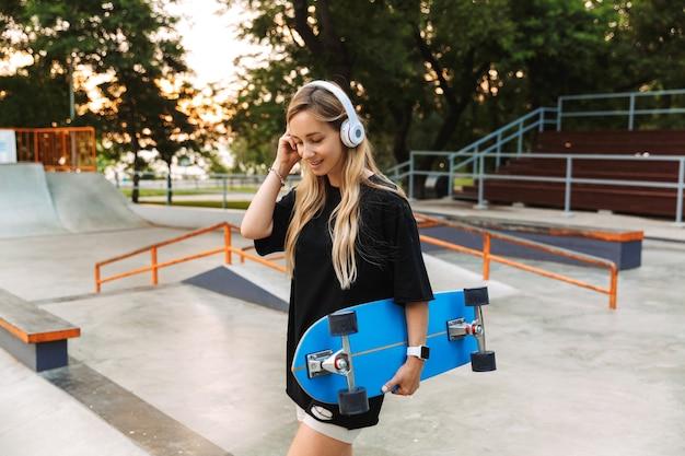Jolie adolescente funky exerçant son longboard en marchant au skatepark