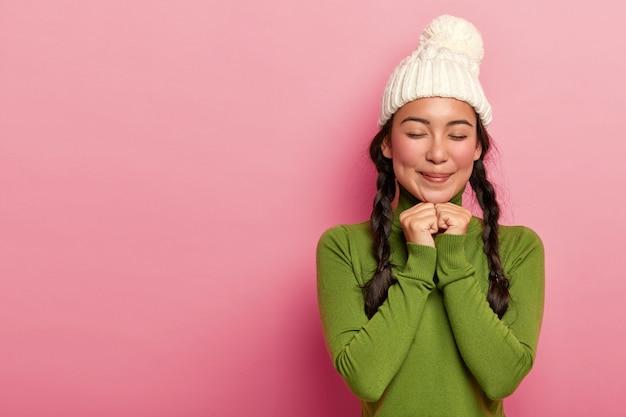 Jolie adolescente garde les mains sous le menton, imagine quelque chose d'agréable