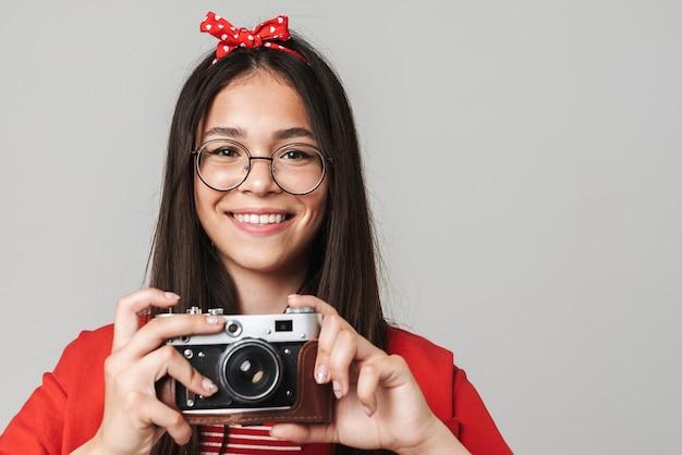 Jolie adolescente heureuse portant une tenue décontractée, isolée sur un mur gris, prenant des photos avec un appareil photo portrait