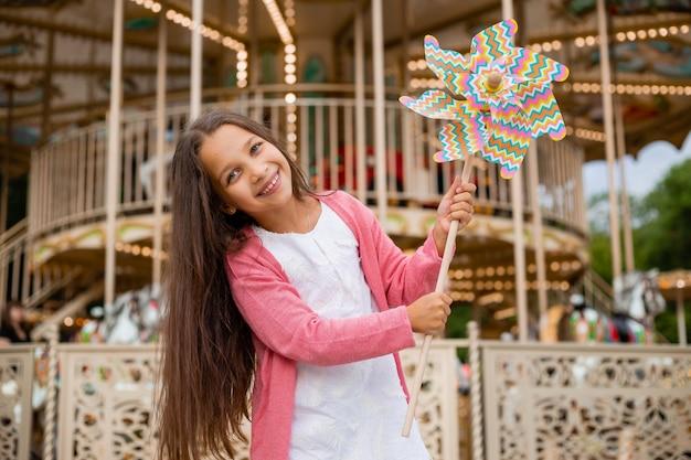 Jolie adolescente joue près du carrousel dans la brise de jouet