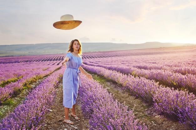 Jolie adolescente marchant dans le champ de lavande et chapeau tombant