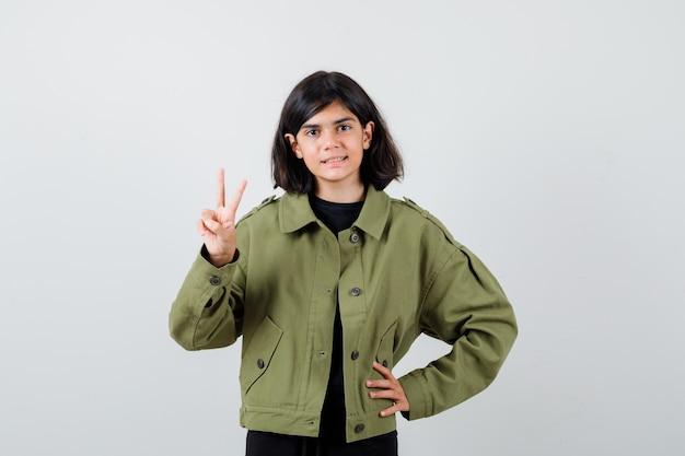 Jolie adolescente montrant un geste de paix en veste verte de l'armée et l'air heureux, vue de face.