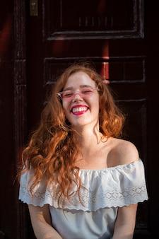 Jolie adolescente posant devant une porte avec des lunettes de soleil