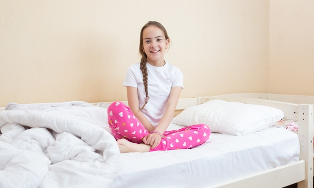 Jolie adolescente en pyjama rose assise sur un lit avec des draps blancs et une couverture