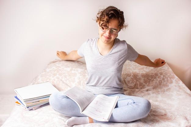Jolie adolescente s'étire sur le lit pendant les cours à domicile
