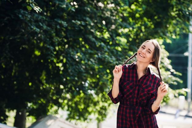 Jolie adolescente en tenue décontractée jouant avec ses tresses, regardant et souriant, debout contre le feuillage vert