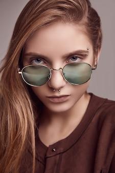 Jolie adolescente en vestes de mode et lunettes de couleurs