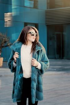 Jolie adolescente vêtue d'un manteau de fourrure naturelle coloré vif et de lunettes de soleil