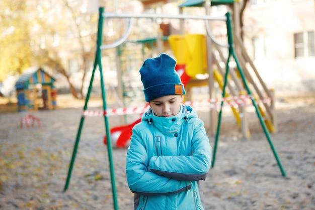 Jolie adolescente vêtue d'une veste bleue et d'un chapeau vert, croisa les bras sur sa poitrine, se lève, triste et regarde vers le bas