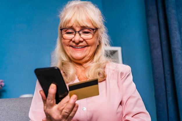 Jolie adulte de plus de 60 ans surfant sur internet avec un appareil smartphone