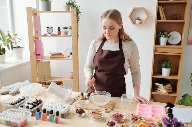 Jolie artisan en vêtements de travail mélange de la masse de savon liquide dans un bol tout en la préparant à verser dans des moules en silicone