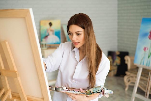 Jolie artiste belle fille peindre une image sur une toile sur un chevalet.