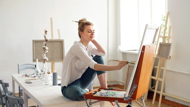 Une jolie artiste blonde peint une peinture à l'huile sur toile à l'aide d'un pinceau et d'une palette