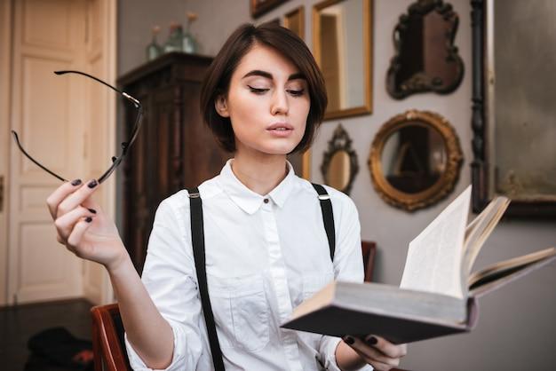 Jolie auteure en chemise blanche lisant un livre et tenant des lunettes à la main