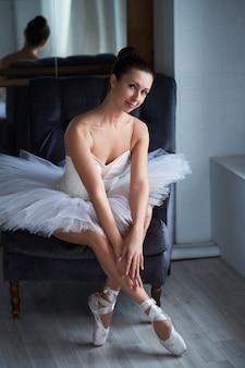 Jolie ballerine assise sur un fauteuil avec ses jambes ouvertes et détournant les yeux pensivement. copyspace