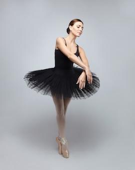 Jolie ballerine pose gracieusement en studio sur fond blanc