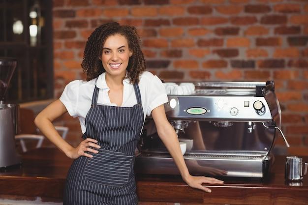 Jolie barista souriant devant une machine à café