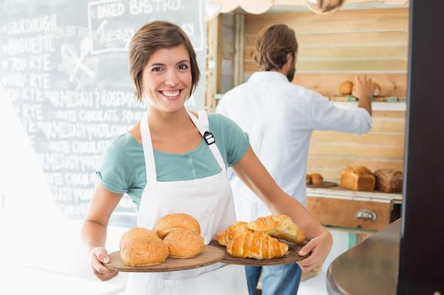 Jolie barista tenant des plateaux de produits de boulangerie