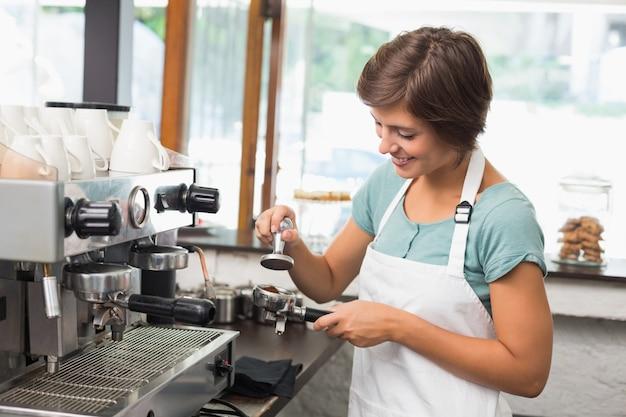 Jolie barista en train de presser des moulins à café