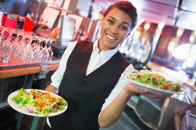 Jolie barmaid tenant des assiettes de salades dans un bar