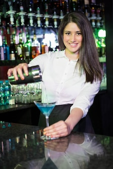 Jolie barman versant un verre de martini bleu dans le verre au bar