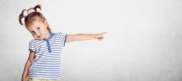Jolie belle belle petit enfant porte un t-shirt rayé, a deux queues de cheval drôles, pointant avec sa petite main