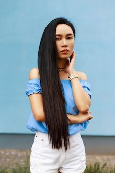 Jolie belle femme asiatique dans un vêtement d'été à la mode debout près d'un mur bleu