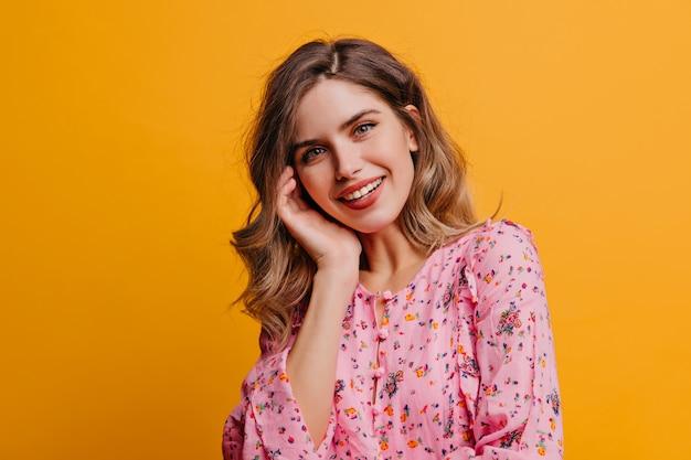 Jolie belle femme aux cheveux ondulés en riant sur le mur jaune. photo intérieure d'une jolie fille blanche porte un chemisier rose.