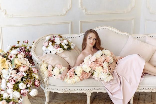 Jolie belle femme dans beaucoup de fleurs est assise sur un canapé beige dans un intérieur clair.